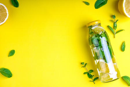 Detox fruit infused water, citrus fruits and mint leaves on yellow background. Flat lay summer background with summer drink. Top view. Copy space Stock Photo - 115147475