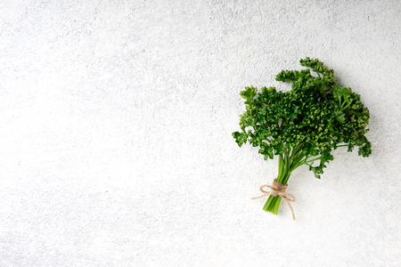Parsley bunch on white concrete background. Fresh parsley herb. Vegetarian food background, top view. Copy space Stock Photo - 115147476
