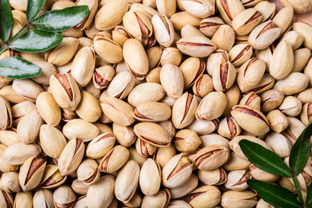 Pistachios nuts background. Pistachio texture with leaves. Nuts. Top view Archivio Fotografico - 115147487