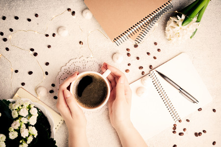 Female hands holding coffee cup. Coffee, flowers, notebooks and led lights, cozy weekend concept, top view. Femininity background, flat lay. Toning. Copy space
