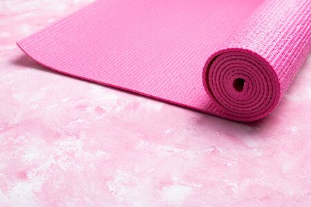 Yoga mat on pink background. Equipment for yoga. Concept healthy lifestyle, sport, meditations and relaxations. Top view, copy space