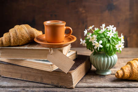 Bouquets of forest flowers, coffee cup, old books, croissants on wooden rustic table. Good morning, breakfast, reading, cozy home, hygge concept