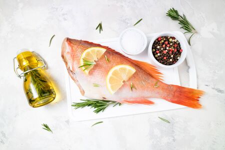 Fish raw snapper with lemon slices, herbs rosemary, salt and pepper on white background. Healthy food and dieting concept. Ingredients for cooking fish. Top view