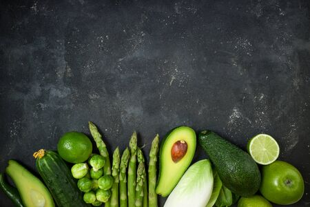Raw healthy food clean eating green vegetables asparagus, avocado, brussels, cucumber, pepper, apple, lime, spinach and chicory on dark stone background, top view. Detox and antioxidant concept. Copy space