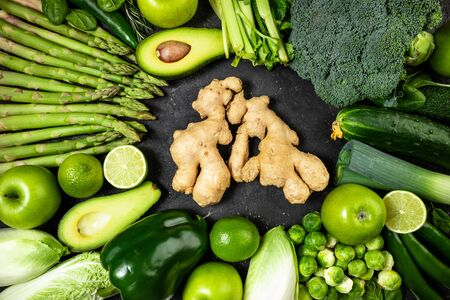 Healthy food clean eating green vegetables, fruits and ginger on dark stone background. Healthy food, healthy lifestyle, dieting, antioxidant, detox concept. Top view