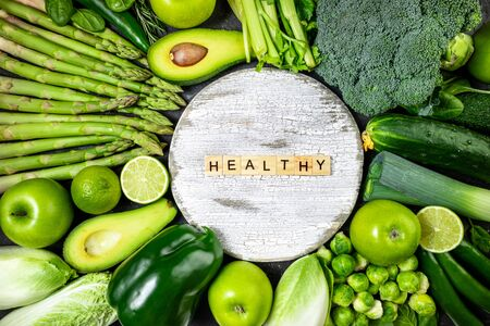 Healthy food clean eating green vegetables and fruits on dark stone background. Healthy food, healthy lifestyle, dieting, detox concept. Top view