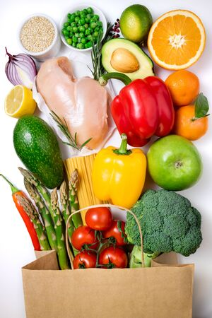 Healthy food background. Healthy food in paper bag meat, fruits, vegetables and pasta on white background. Shopping food in supermarket, dieting concept. Top view Stok Fotoğraf