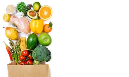 Healthy food background. Healthy food in paper bag meat, fruits, vegetables and pasta on white background. Shopping food in supermarket, dieting concept. Long format with copy space