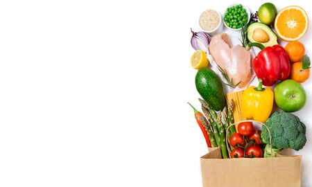 Healthy eating background. Healthy food in paper bag meat, fruits, vegetables and pasta on white background. Shopping food in supermarket, dieting concept. Long format with copy space