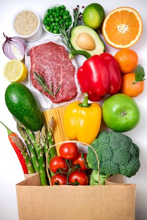 Healthy food background. Healthy food in paper bag meat, fruits, vegetables and pasta on white background. Shopping food supermarket concept. Top view
