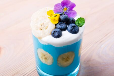 Smoothie dessert with fruits, berries, nuts and flowers on wooden background. Tropical healthy smoothie. Healthy breakfast, vegetarian food, lunch concept