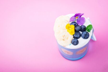 Blue smoothie with banana fruits, blueberries and eating flowers. Tropical healthy smoothie dessert. Healthy breakfast, vegetarian, dieting concept. Top view, flat lay, copy space 免版税图像