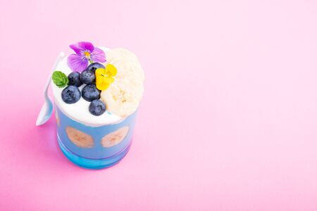 Smoothie dessert with fruits, berries, nuts and flowers on pink background. Tropical healthy smoothie. Healthy breakfast, vegetarian food, lunch concept