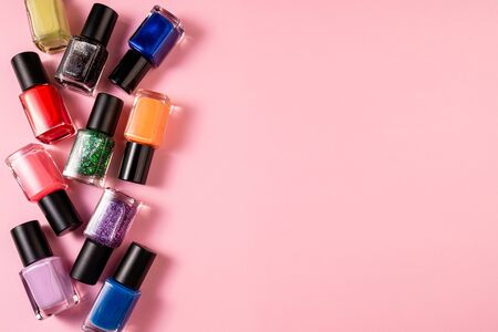 Set of various nail polish bottle on pink background with copy space. Stylish trendy nail polish for female manicure. Colorful nail lacquer top view