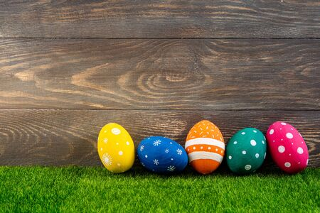 Happy Easter background. Easter eggs on the grass with wooden background. Festive decoration. Copy space