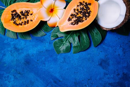 Summer tropical background with exotic fruits papaya and coconut, green palm leaves on blue. Fruits background. Top view, copy space