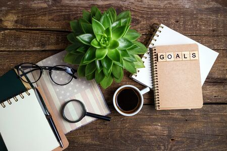 New year 2020 goals list. Office desk table with cup of coffee, american flag on old book, succulent, pen, notebook and magnifier. Goal, plan, strategy, resolutions concept