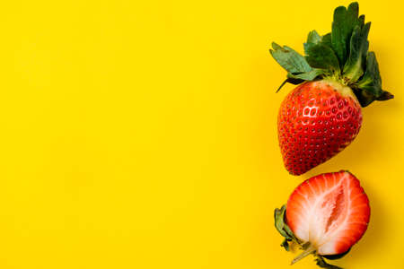 Strawberry on yellow background. Summer berries background. Tropical background. Healthy food concept. Copy space