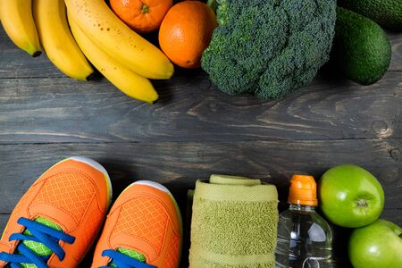 Sport shoes, bottle of water, fruits and vegetables on wooden background. Set of sport equipment and healthy food. Concept healthy lifestyle, sport and diet. Top view, copy space