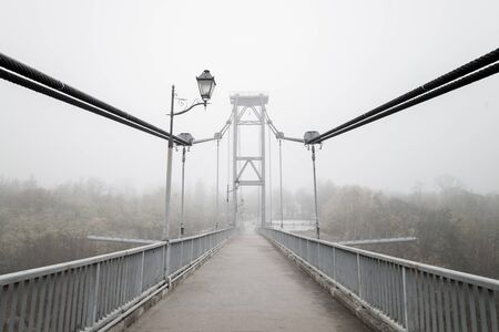 Bridge with fog in grey tones. Melancholy misty landscape with bridge and lamps. Season, weather, mood concept