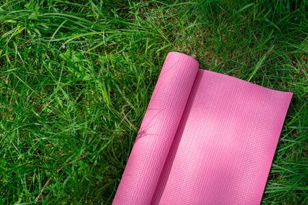Pink yoga mat on fresh green grass. Equipment for yoga. Concept healthy lifestyle, sport and wellness. Copy space