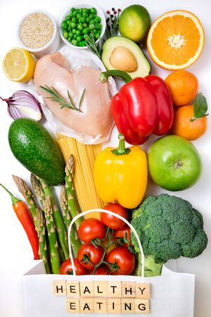 Healthy eating background. Healthy food in paper bag meat, fruits, vegetables and pasta on white background. Shopping food in supermarket and meal planning concept