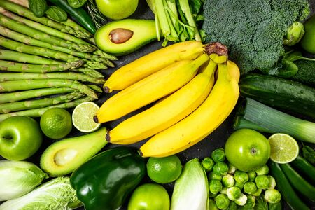 Healthy food clean eating green vegetables and fruits on dark stone background. Healthy food, dieting, detox concept. Top view