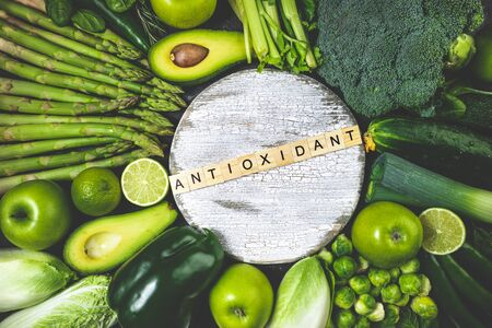 Healthy food clean eating green vegetables and fruits on dark stone background. Healthy food, dieting, antioxidant, detox concept. Top view