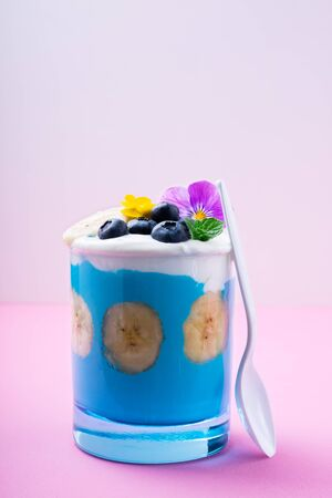 Blue smoothie with banana fruits, blueberries and eating flowers on pastel pink background. Tropical healthy smoothie dessert. Healthy breakfast concept. Top view, flat lay, copy space 免版税图像