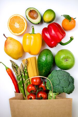 Healthy food background. Healthy food in paper bag fruits, vegetables and pasta on white background. Shopping food in supermarket, vegetarian concept. Top view