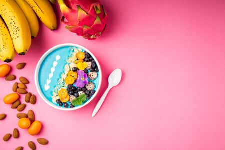 Smoothie bowl with fruits, berries, nuts and flowers on pink background. Tropical healthy smoothie dessert. Healthy breakfast, vegetarian food, lunch concept. Top view, flat lay