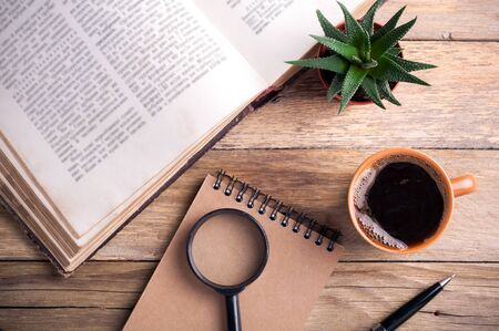 Coffee cup, open book, succulent aloe, pen, notebook and magnifier on rustic wooden background. Office desk table. Educations concept. Top view Stock fotó