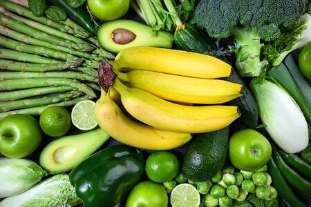 Raw healthy food clean eating vegetables and fruits asparagus, broccoli, avocado, banana, brussels, cucumber, pepper, celery, apple, lime, spinach and chicory on dark stone background, top view Stok Fotoğraf