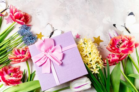 Femininity background with tulips, spring flowers and gift box. Spring background. Floral pattern. Greeting card, holidays, Easter, Mother's day, 8 March, Happy birthday concept. Flat lay, top view