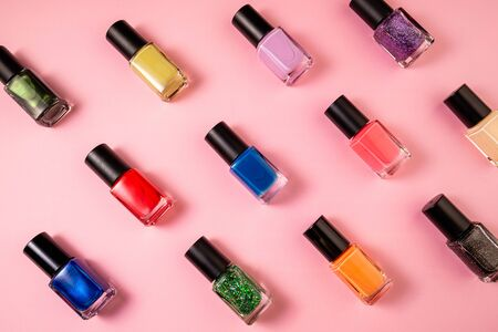 Pattern of various nail polish bottle on pink background. Stylish trendy nail polish for female manicure. Set of colorful nail lacquer top view