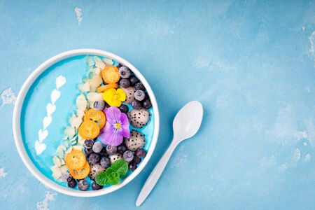 Smoothie bowl with fruits, berries, nuts and flowers. Tropical healthy smoothie dessert. Healthy breakfast, vegetarian, dieting concept. Top view, flat lay 免版税图像