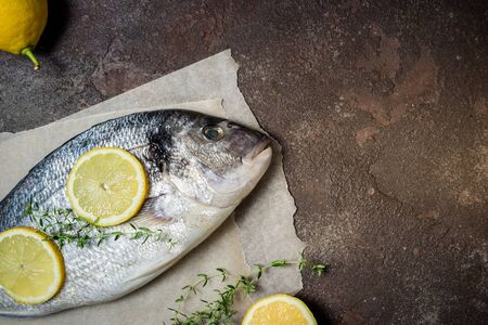 Fresh raw fish closeup. Dorado fish with lemon and thyme on kitchen table. Cooking fish with herbs. Top view, copy space