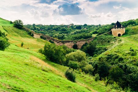 Summer view of green hills and old watchtower ruins. Khotyn Fortress location. Dramatic scene of green hills landscape. Traveling concept background