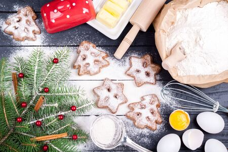 Baking background. Ingredients for cooking christmas baking - flour, egg, spices and butter. Christmas tree. Top view