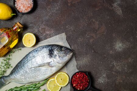 Fresh fish dorado and ingredients for cooking. Raw fish dorado with aromatic spices, herbs, lemon and vegetables. Sea bream fish cooking. Copy space