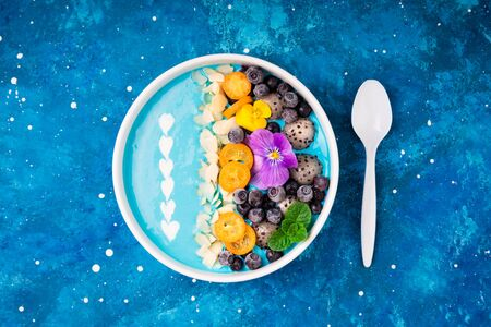 Blue smoothie bowl with fruits, berries, nuts and flowers. Tropical healthy smoothie dessert. Healthy food, vegetarian, diet concept. Top view 版權商用圖片