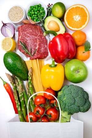 Healthy food background. Healthy food in paper bag meat, fruits, vegetables and pasta on white background. Shopping food in supermarket concept