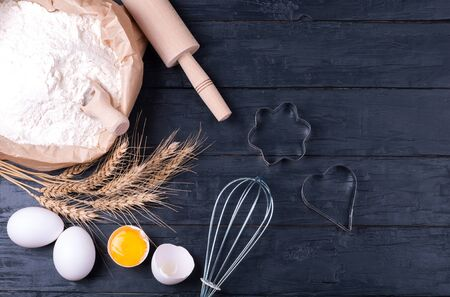 Ingredients for baking. Flour in paper bag, wheat eggs and kitchen utensils - rolling pin and whisk on dark wooden background. Cooking cookies. Top view. Copy space