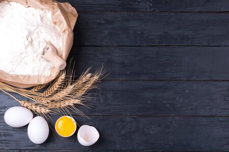 Baking background. Flour in paper bag, wheat and eggs on dark wooden table. Ingredients for cooking homemade baking. Top view. Copy space