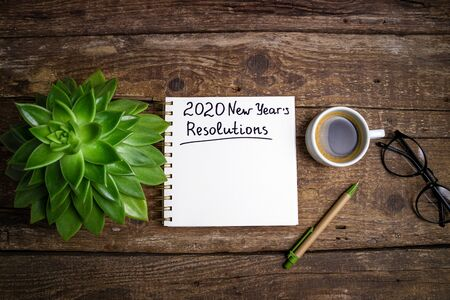 New year resolutions 2020 on desk. 2020 goals list with notebook, coffee cup and eyeglasses on wooden background. Goal, plan, strategy, change, idea concept. Top view 版權商用圖片