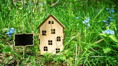 Wooden house on green grass. House for sale. Real estate, family home, eco friendly house concept