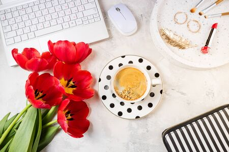 Stylish trendy feminine workspace flat lay. Female home office with laptop, flowers, coffee cup, accessories and cosmetics on table top view. Femininity, fashion, beauty concept 版權商用圖片