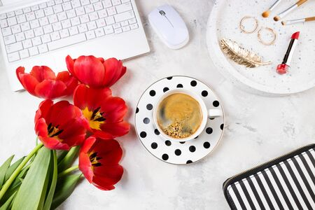 Fashion feminine workspace flat lay. Female home office with laptop, flowers, coffee cup, accessories and cosmetics, notepad on stone background. Feminine background. Top view 版權商用圖片