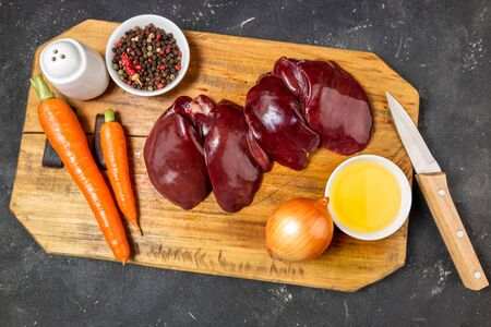 Raw liver with spices, vegetables carrots and onion on dark stone background. Ingredients for cooking liver for pate. Food background. Top view