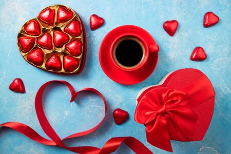 Valentines Day background with red heart, chocolate bonbons and coffee cup. Heart shape from ribbons. Top view